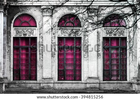 Facade of old abandoned building with three large arched windows of pink glass. Monochrome background - stock photo