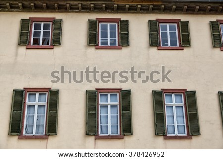 facade of  old building.  ancient windows with wooden shutters on the light wall.