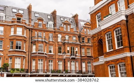 Facade of opulent  British Victorian Edwardian terraced flat in red bricks in Chelsea, London. - stock photo