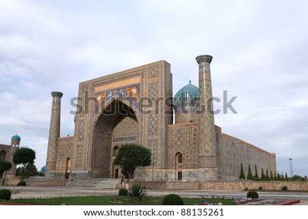 Facade of Sher Dor Madrasah. It was constructed from 1619-1636 in Samarkand, Uzbekistan. Ribbed domes on high towers soared over the two-storied facade on the sides of the front portal.
