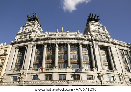 Facade of the Banco de Bilbao building with statues on the roof on Calle de Alcala in Madrid, Spain