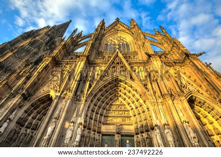 Facade of the Dom church in the city Cologne lit by evening sun - stock photo