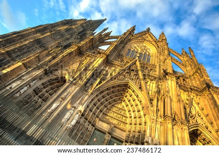 Facade of the Dom church in the city Cologne with blue sky and evening sun - stock photo