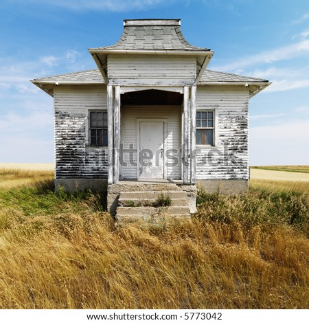 Facade of weathered abandoned building with peeling paint in grasslands. - stock photo