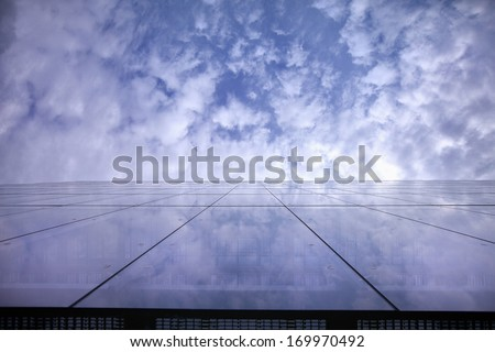 Facade reflecting a lightly clouded blue sky - stock photo