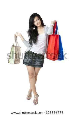 Facade shot of a young girl with shopping bags on her hands isolated in a white background