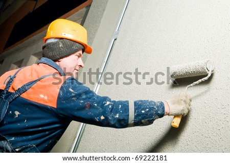 facade worker at decoration plastering works outside building wall with roller - stock photo