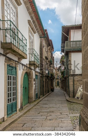 Facades and medieval buildings and alleyway near the Santiago Square, also known as Sao Tiago or Sao Thiago, in the Historical Center of Guimaraes, Portugal. Unesco World Heritage Site. - stock photo