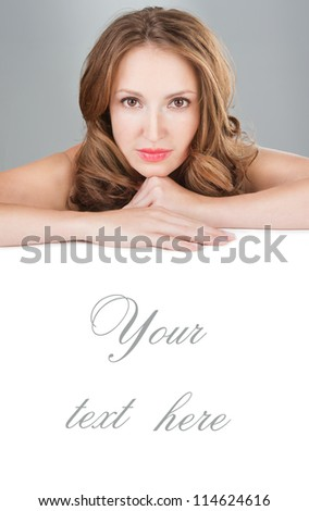 Face beauty skin. Beautiful woman lay on hands with a manicure, daily fresh make-up and wavy hairstyle.  Empty copy space for text on the banner. SPA. Vertical. Grey background. Studio shot. - stock photo