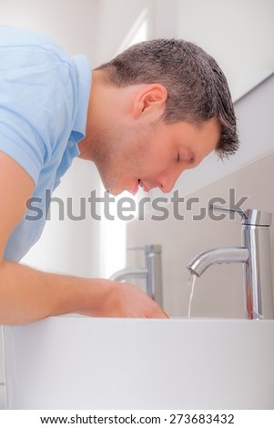 face cleaning male in bathroom - stock photo