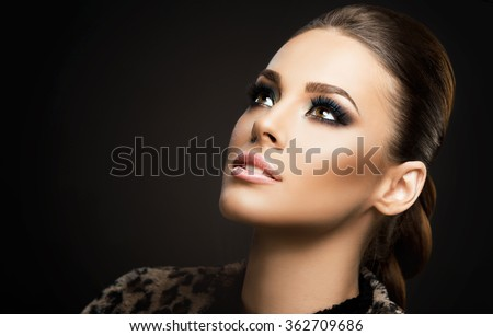 Face close-up of a beautiful young woman isolated on dark background; perfect skin, beauty portrait - stock photo