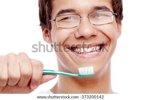 Face close up of young hispanic man wearing glasses holding toothbrush near his toothy smile with perfect healthy white teeth isolated on white background - dental care and hygiene concept - stock photo