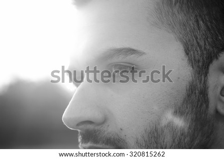 face close up of young men, strong sun light and lens flare. - stock photo