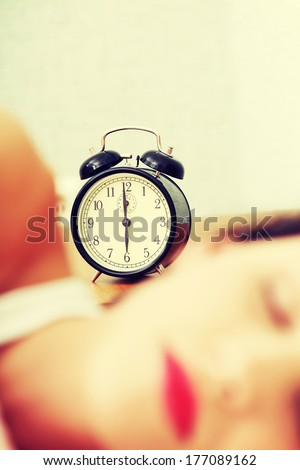 Face closeup of a young beautiful woman sleeping in bed, with a black alarm clock in the background - zoom in on the alarm clock. - stock photo