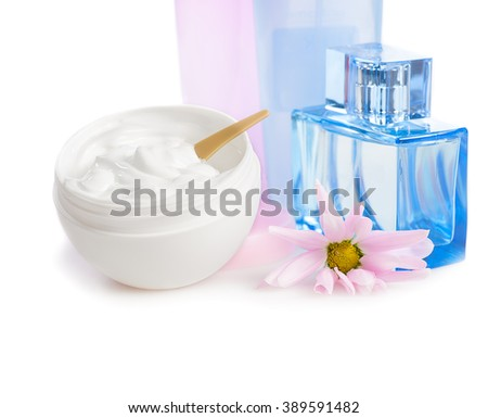 face cream in  white jar with pink flower and blue  glass vial  of toilet water on white background - stock photo