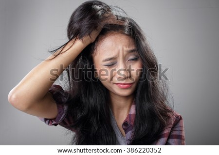 Face expression of young Asian woman having a painful migraine, holding her head in frustration - stock photo