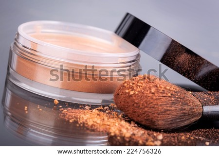 Face foundation powder product with crumbled texture. Focus on jar