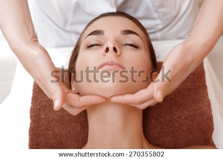 Face lifting massage. Close-up of a masseuse hands massaging face of a young female client of a spa salon  - stock photo