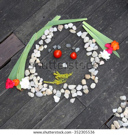 Face made of stones on a wooden background - stock photo