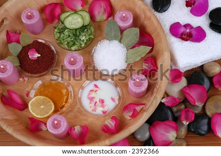 Face masks, bath salt, body scrubs, petals, orchids, towels, and pebbles in a spa - stock photo