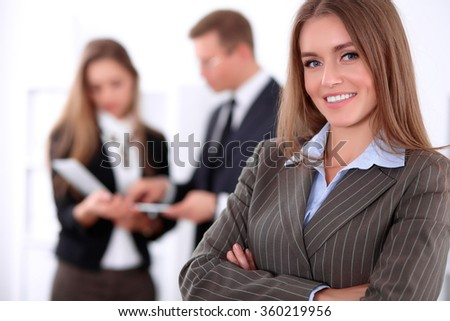 Face of a beautiful cheerful smiling business woman on the background of colleagues - stock photo