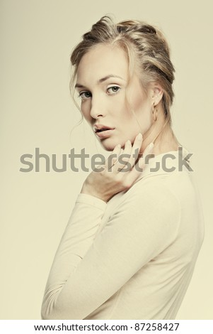face of a beautiful girl with perfect skin with a hand from a person on a yellow background, sepia - stock photo
