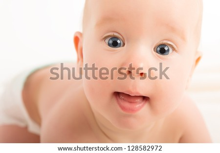 face of a beautiful happy baby with blue eyes - stock photo