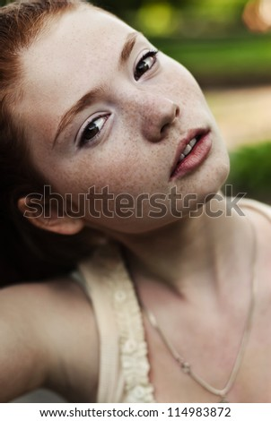 face of a beautiful young girl with freckles - stock photo