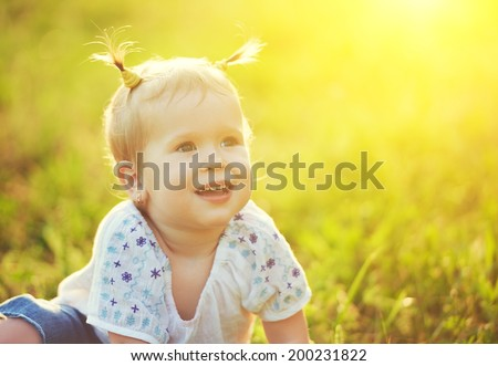 face of a happy beautiful baby girl on nature summer - stock photo
