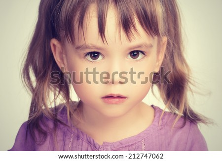 face of a little beautiful girl with sad eyes - stock photo