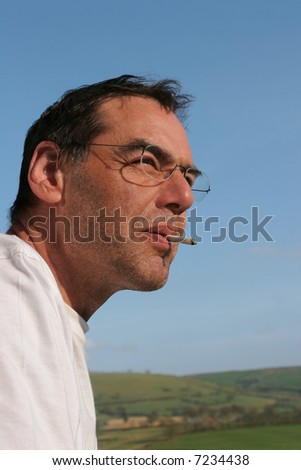 Face of a middle aged man wearing glasses, smoking a cigarette and looking thoughtful. Set against a blue sky.