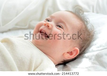 Face of a newborn baby smile in his baby cot. Concept photo of newborn, baby, mother, motherhood, parenting and lifestyle - stock photo
