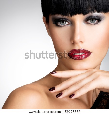 Face of a woman with beautiful dark nails and sexy red lips. Fashion model with black shot hairs at studio - stock photo