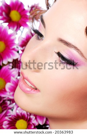 Face of a young beautiful woman. Flowers on the background - stock photo