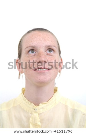 Face of a young girl with freckles with her eyes open, as if in prayer. - stock photo