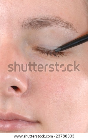 Face of a young woman doing her makeup