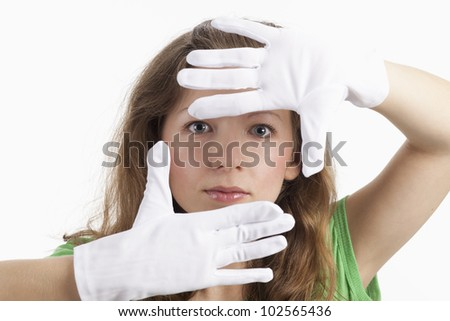 Face of a young woman surrounded by white gloves - stock photo