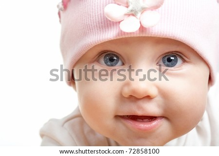 Face of adorable baby in hat looking at camera - stock photo