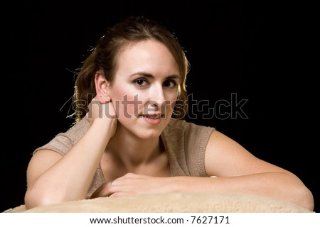Face of an attractive brunette woman leaning on arms over black