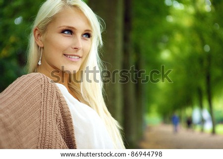 Face of an attractive confident self-assured young blonde woman in a tree-lined park avenue. - stock photo