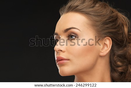 face of beautiful beautiful woman over black background - stock photo