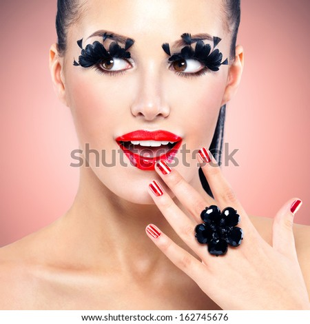 Face of beautiful fashion woman with red sexy lips and  black false eyelashes at studio - stock photo