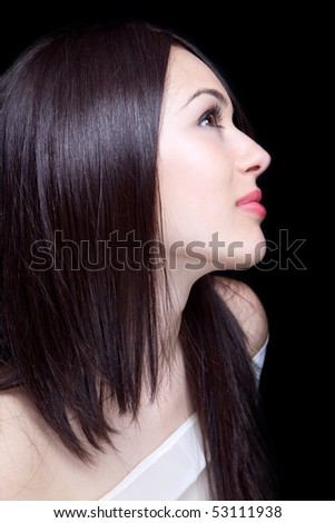 Face of beautiful sexy young brunette woman over black