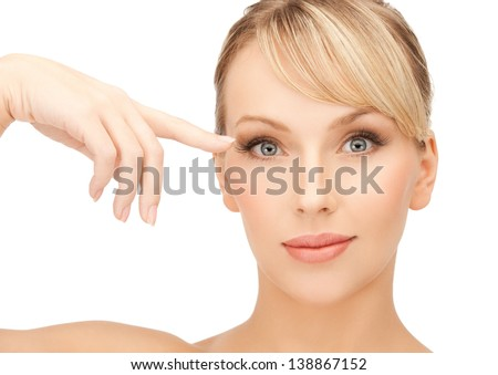 face of beautiful woman touching her eye area - stock photo