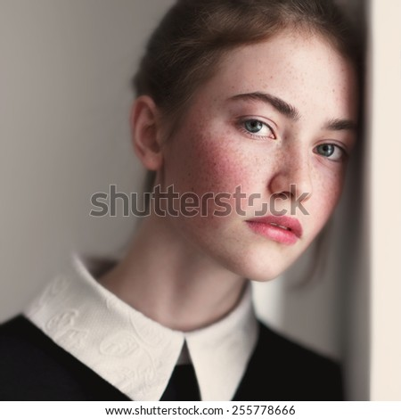 face of beautiful young girl close-up house near the window - stock photo