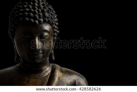 face of brass Buddha statue, low key light, black isolated background, copy space on right side. - stock photo