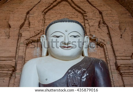 Face of Buddha isolated on a brick background .