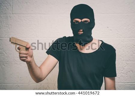 Face of burglar wearing a black ski mask or balaclava with a gun in his hand - stock photo