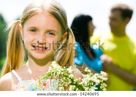 Face of cheerful girl looking at camera with smile on background of her father and mother - stock photo