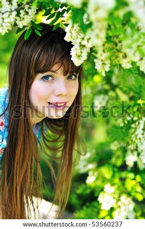 face of cheerful pretty girl standing near blossom of acacia - stock photo